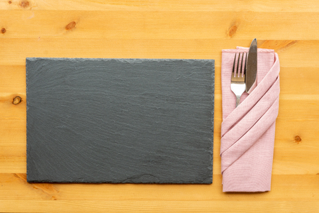 A top view of a slate place mat with knife fork in a folded napkin on a wooden table top Stockfoto