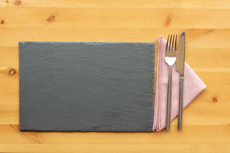 A top view of a slate place mat with knife and fork beside it on a folded napkin on a wooden table top