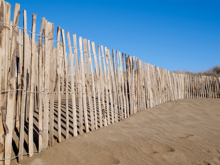 A wooden fence keeps people out of an area of sand dunes on a beach