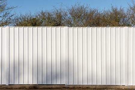Two panels of a white metal fence used to screen off a wooded site