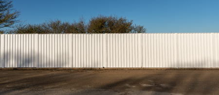 A long white metal fence used as a screen around a building site
