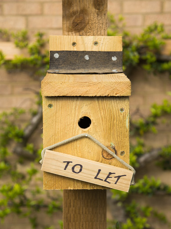 A vacant blue tit nesting box with a To Let sign awaiting new tenants in the spring