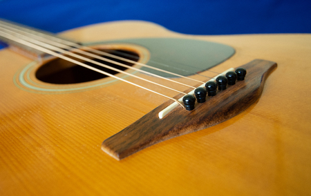 Close up of an acoustic guitar bridge with sound hole and finger plate in background Zdjęcie Seryjne