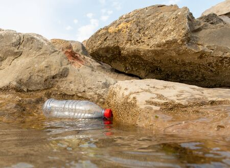 A discarded plastic water bottle is washed up on shore line between rocks Zdjęcie Seryjne