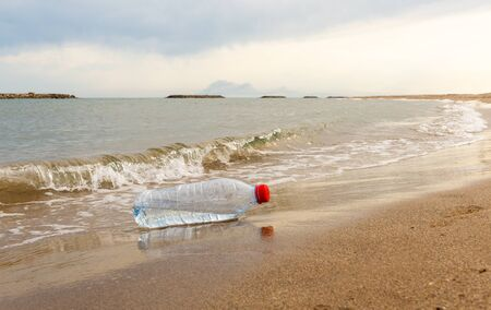A discarded plastic water bottle is washed up on a sandy beach