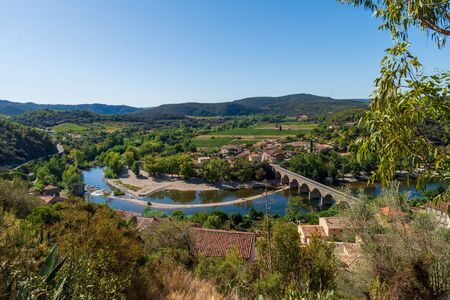 Landscape of the bend and bridge on the river Orb leading into the village of  Roquebrun  in the Haut Languedoc, France
