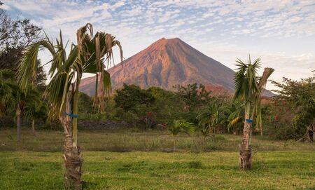 Landscape view of Conception volcano in Nicaragua Central America with palm trees in the foreground