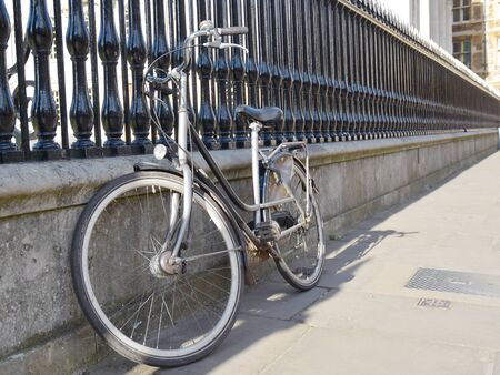 A student bicycle is resting against railings in the university town of Cambridge IK