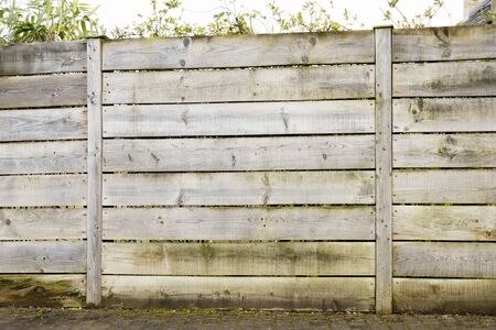 One panel of a weathered wooden fence made up of horizontal planks