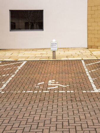 A visitor parking bay reserved for the disabled with wheelchair symbol and a post with sign outside an office building Zdjęcie Seryjne