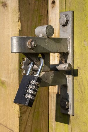 A combination style padlock used to secure a wooden gate Zdjęcie Seryjne