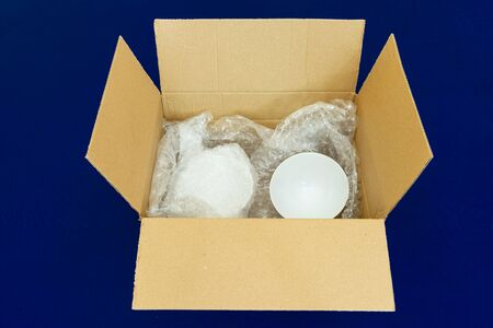 Fragile and breakable items wrapped up in protective packaging and placed in a box ready for shipping
