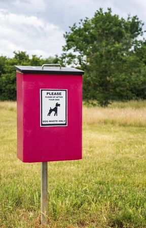 A clearly signed red dog waste bin on a post in a country park