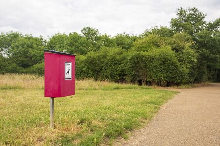A red bin for dog excrement sits beside a footpath in a rural country park Zdjęcie Seryjne