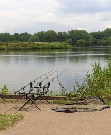 Three fishing rods with reels on a stand with an unhooking mat on a platform beside a picturesque lake waiting for a fish to take the bait