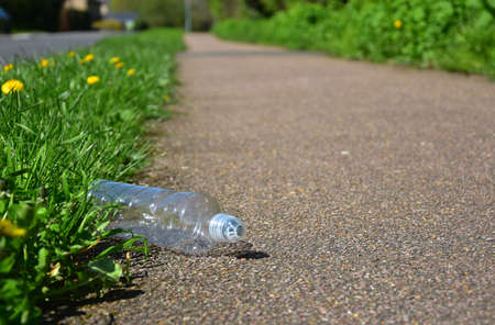 A carelessly throw away plastic water bottle nestled in the foliage litters a roadside path or cycleway
