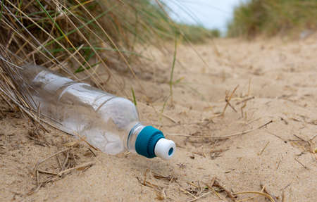 A carelessly discarded plastic drinks bottle lies amongst sand and sedge grass in fragile dunes at a beach causing pollution Zdjęcie Seryjne