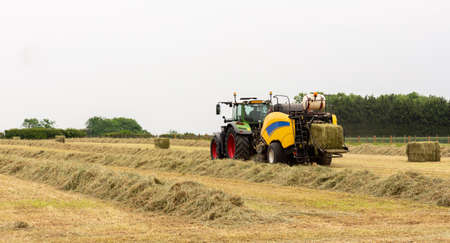 A tractor works in a field bailing straw Stock fotó
