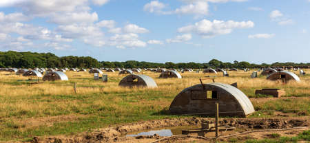 A field of shelters for pigs being raised healthily in the open air on a farm