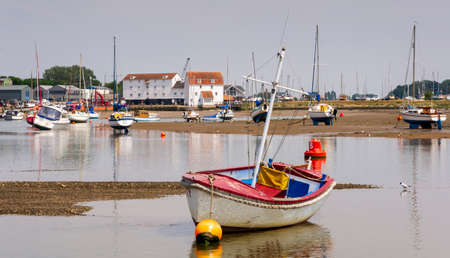 Safety boat lies in shallow water in front of the tide Mill at Woodbridge on the Deben Estuary in Suffolk UK