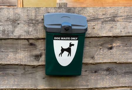 A green dog waste bin with clear signage is mounted on a weathered wooden fence