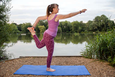 A mature female yoga teacher demonstrates the Dancer pose beside a tranquil lake Stock fotó