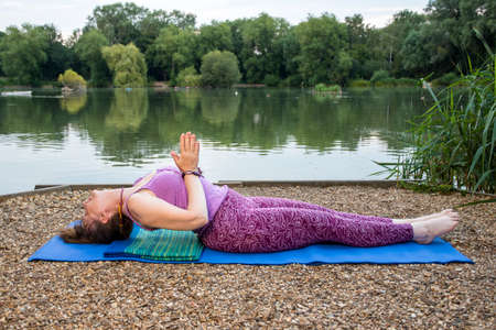 A mature female yoga teacher relaxes in the fish pose beside a tranquil lake