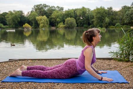 A mature female yoga teacher demonstrates the cobra pose beside a tranquil lake