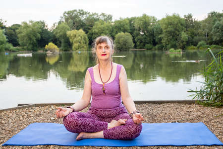 A mature female yoga teacher demonstrates the Half Lotus pose beside a tranquil lake