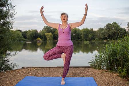 A mature female yoga teacher demonstrates the Tree pose with extended arms beside a tranquil lake