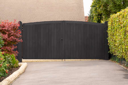 A black, wooden gate bars entry from hedge lined driveway
