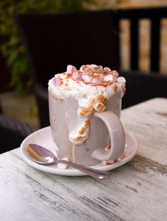 A mug of indulgent hot chocolate on a table topped with cream and marshmallows overflows into its saucer