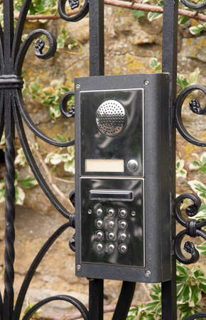 An entry intercom with kepyad is mounted on an ornate fence Stock fotó