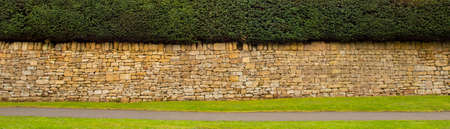 A cotswold stone wall topped with a hedge with a path and strip of grass in front suitable for a banner