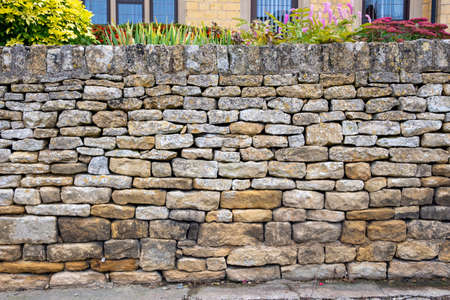 A cotswold dry stone wall in front of a house