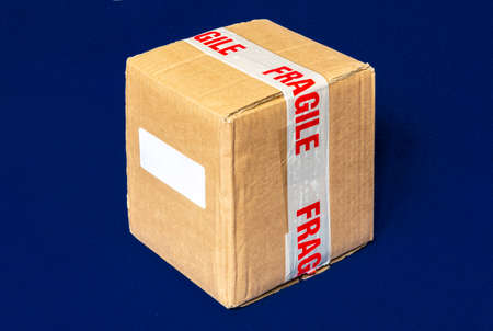 A cardboard shipping box, securely wrapped with tape indicating the contents are fragile