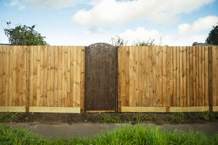 A closed gate in a wooden feather edge fence beside a path