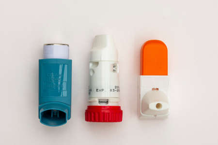 Three isolated asthma inhalers, emergency and preventers used to treat the chronic condition in lay-flat representation
