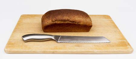 A loaf of healthy freshly home baked wholemeal bread sits on a chopping board with knife ready to be cut. Stock fotó