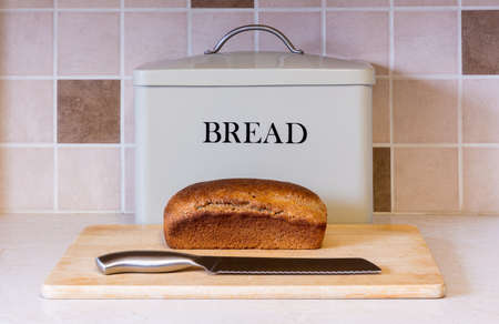 A loaf of freshly baked wholemeal bread sits on a bread board in front of a storage tin with knife ready to be cut