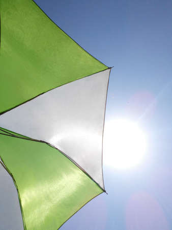 palapa: green and white umbrella over blue sky Stock Photo