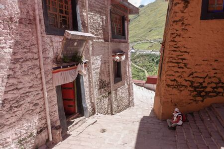 Drepung monastery just 8 km away from Lhasa, Tibet, Asia, white and red buildings, woman sitting and resting