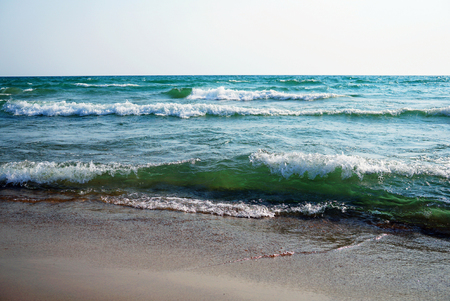 Raging sea on a sunny windy day. Large waves with white foam on the crest rise above the surface of the water and run to the shore. Beautiful bright green water is visible in the depths of the waves. Lake Michigan, a beach in the city of Grand Haven.