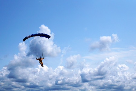 Skydiver under a dark blue little canopy of a parachute on the background a blue sky and clouds, closeup. Silhouette of the skydiver with parachute against the sky & stormy clouds.