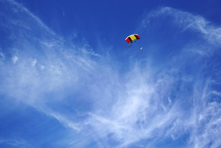 Red yellow parachute canopy and tandems skydivers against the background of smoky clouds and a Bright blue sky. Tandem master with passenger is flying and prepearing to landing. Stock Photo