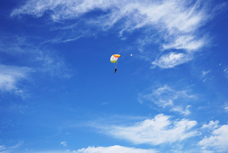 White-orange parachute canopy and tandems skydivers against the background of a lighty clouds and a blue sky. Tandem master with passenger is flying and prepearing to landing. Stock Photo