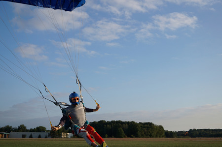Skydiver under a dark blue little canopy of a parachute is landing on airfield, close-up. High-speed landing of a parachuter against the background of forests and buildings.