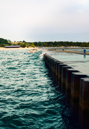 Waves hit the jetty. The water rose above the surface of the pier and covered it. USA, state of Michigan, Michigan Lake. Imagens