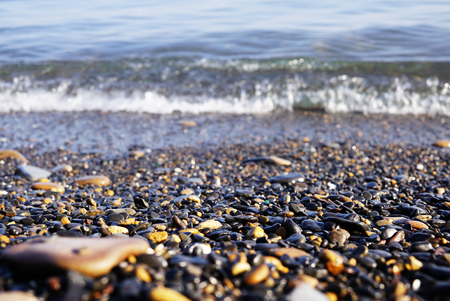 On the seashore there are many small stones of different shapes. sea surf and waves visible behind sea pebbles. Far East of Russia, Vladivostok