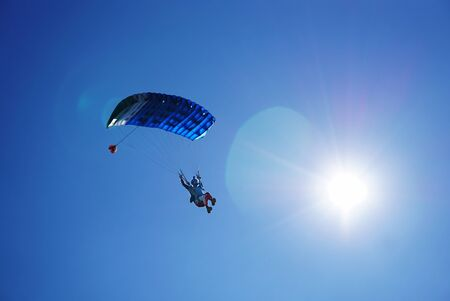 Skydiver under a blue little canopy of a parachute on the background a sun and a blue sky, close-up. Silhouette of the skydiver with parachute against the highlight